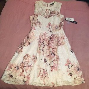 A white laced dress with a pink flower pattern
